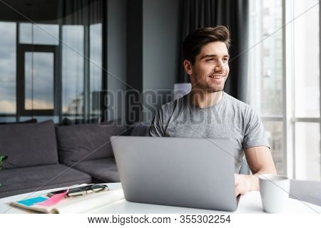 Handsome smiling young bearded man wearing casual clothes using laptop computer while sitting at the table at home