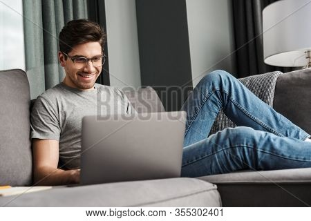 Portrait of an attractive smiling young bearded man wearing casual clothes sitting on a couch at the living room, using laptop computer