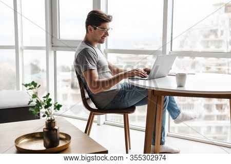 Handsome young bearded man wearing casual clothes using laptop computer while sitting at the table at home