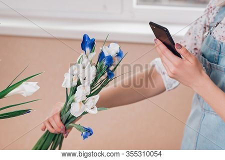 Young Woman Florist Taking Pictures Of Fresh Flowers Of Fleur-de-lises On Smartphone.