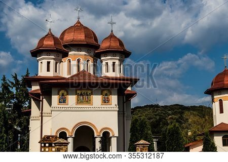 White Church With Painted Facade, Copper Roof Towers With Crosses On Top, Forest In The Background A
