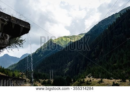 Water Dripping Over A Mountain Tunnel With Power Lines, Mountain Forest And Puffy Clouds Above