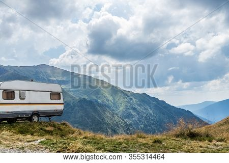 Caravan Parked On The Ledge Of A Mountain Road With Mountains In The Background And Puffy Clouds Abo