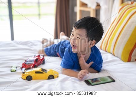 Asian Boy Fun And Play A Toy And Smart Phone On The Bed Room.