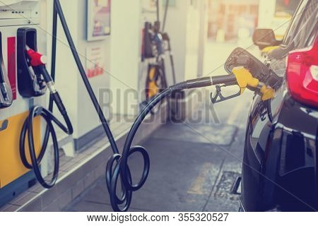Refilling The Car With Fuel At The Gas  Station And Blurry Staff Background,  Refilling The Car With
