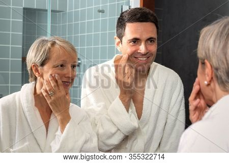 Close Up Portrait Of Middle Aged Couple In Bathrobes Looking In Bathroom Mirror. Couple Reviewing Sa