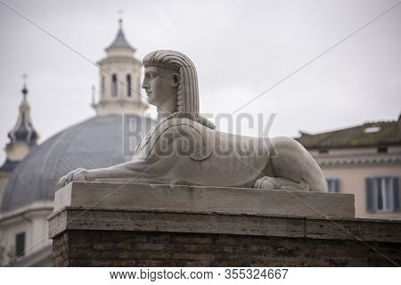 The Sphinx Statue In The Lion Fountain In Piazza Del Popolo, Rome, Italy. In The Background The Twin