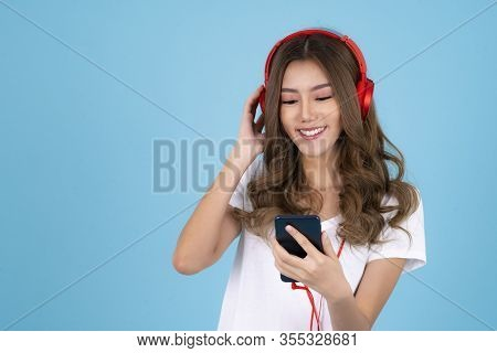 Asian Woman With Headphones And Listening To Music On A Blue Isolated Background
