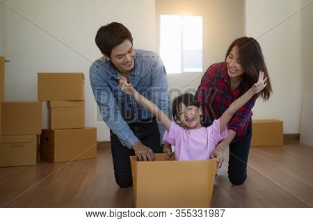 Happy Asian Family With Cardboard Boxes In New House At Moving Day.