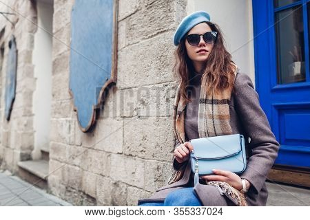 Portrait Of Stylish Young Woman Wearing Beret Coat Holding Blue Purse Outdoors. Spring Fashion Femal