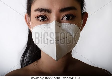 Close Up Of A Woman Putting On A Respirator N95 Mask To Protect From Airborne Respiratory Diseases A