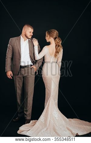 Stock Photo - Portrait of beautiful young wedding couple at black background