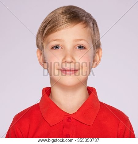 Photo of adorable young happy boy looking at camera. Closeup face of a cute blond boy over white background. Portrait of white smiling kid in a red t-shirt. Pretty kid with a white an easy smile.