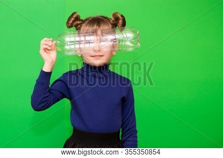 Little Environmentalist Girl Isolated On Green Background Looking Through Plastic Bottle And Shows I