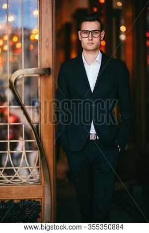 A portrait of a goodlooking young guy walking in the street. Formal men fashion.