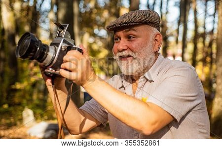 Look At This. Happy Pensioner Hold Camera In Nature. Professional Photographer With Camera. The Phot