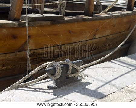 Metal Mooring Post With A Knotted Rope In Front Of A Moored Wooden Boat At A Sea Marina