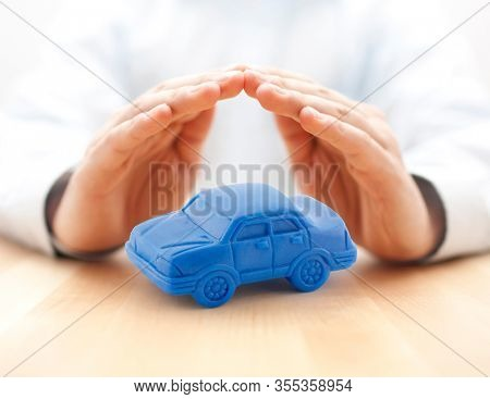 Car insurance concept with blue car toy covered by hands