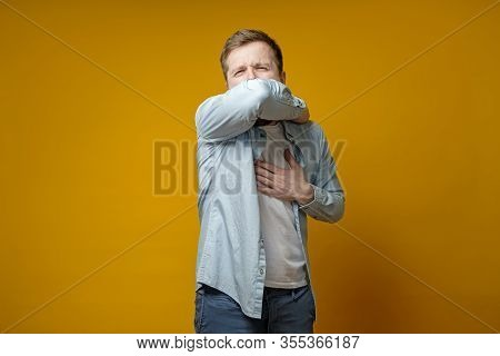 Young Man Coughs At His Elbow And Holds Hand On Chest, Experiencing Pain. Correct Sneezing. Concept