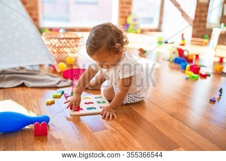 Adorable toddler learning numbers using maths puzzle around lots of toys at kindergarten