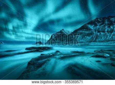 Northern Lights Over Snowy Mountains, Sea Coast With Sandy Beach And Stones In Blurred Water In Lofo