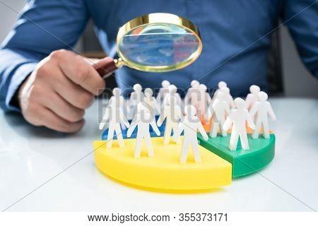 Businessperson Analyzing Market Segment Using Magnifying Glass
