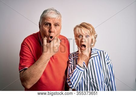 Senior beautiful couple standing together over isolated white background Looking fascinated with disbelief, surprise and amazed expression with hands on chin