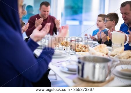 Eid Mubarak Muslim people praying before iftar dinner. Eating traditional  food during Ramadan feasting month at home. The Islamic Halal Eating and Drinking at modern western Islamic family.