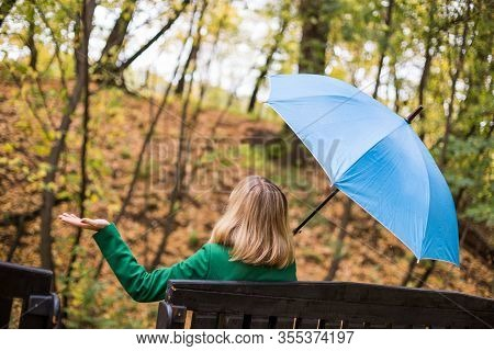 Woman Holding Blue Umbrella And Checking For Rain While Sitting In The Park.