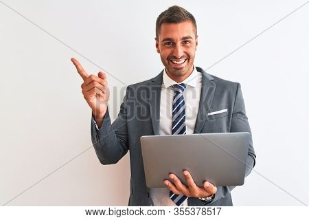 Young handsome business man working using computer laptop over isolated background very happy pointing with hand and finger to the side