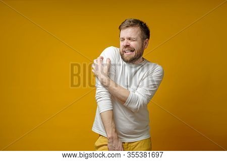 Tense Bearded Man Scratches The Itchy Skin On Arm, Through Clothes, Painfully Grins Teeth And Squint