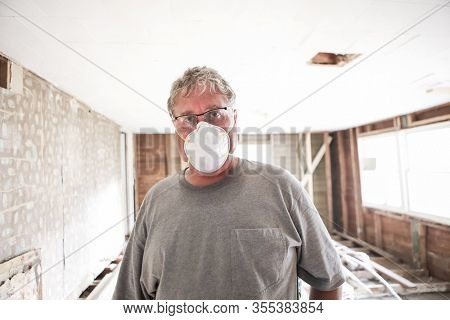Older construction worker wearing safety mask during demo, focus on mask