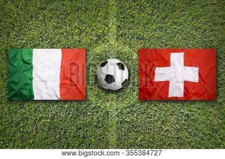 Italy Vs. Switzerland Flags On Green Soccer Field