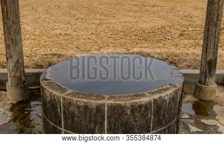 Old Water Well Constructed Of Cement Block Full Of Water In A Mountainside Public Park With Plowed F