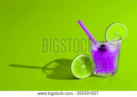 Amazing Purple Pink Cocktail Of The Future With Lime, Ice And Chia Seeds In Glass On Crazy Green Bac