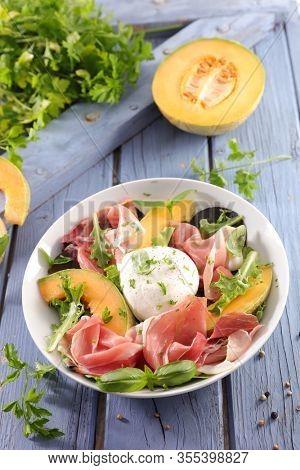 summer salad with cantaloupe, prosciutto ham and mozzarella