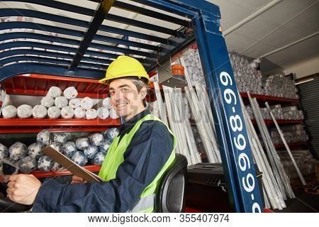 Smiling forklift driver on the forklift in warehouse in shipment