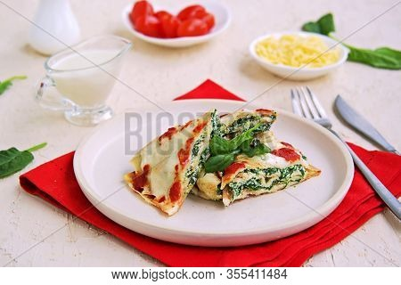 Crepes With Spinach And Ricotta Cheese, Baked With Bechamel Sauce And Tomato Sauce On A White Plate