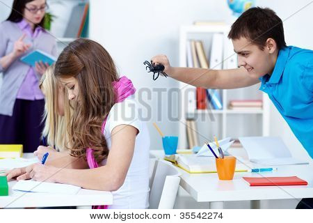 Evil lad holding black spider and going to frighten his classmates at lesson