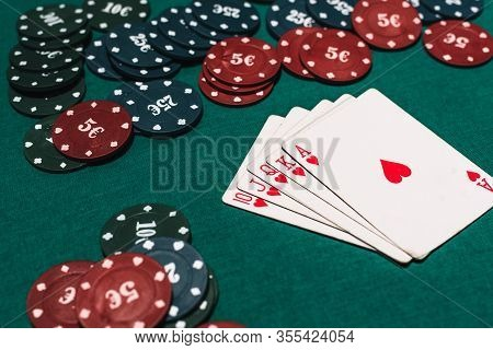 Casino Poker Gambling And Winning Combination. Royal Flush And A Bet Of Chips On Table Background
