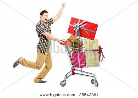 Full length portrait of a happy man pushing a shopping cart full of gifts, isolated on white background