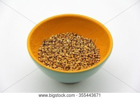 Ceramic Bowl With Buckwheat On A White Background, Top View. The Concept Of Healthy Nutrition, Diets