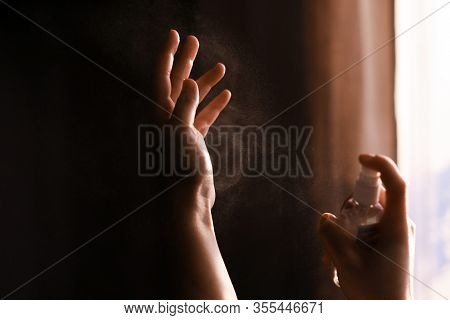 Disinfecting Hands. Person Using Antiseptic Spray On Hands To  Prevent Coronavirus Or Flu Disease. P