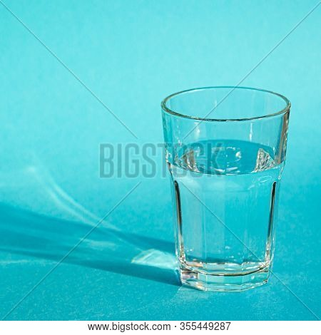 A Glass With Clean Clear Clear Water Stands On A Blue Background With Green Shadows. Clean Water