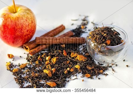 Tea Herbs With Dry Fruit, Cinnamon Sticks, Apple Glass Cup On White Background.
