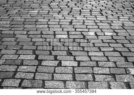 Old European Courtyard, Paved With Gray Cobblestones. Pavers Texture. A Perspective View Of The Mono