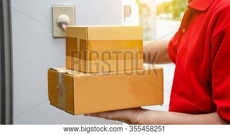 Young Delivery Man In Red Uniform Standing With Parcel Post Box Press Ring Bell In Front Of The Hous