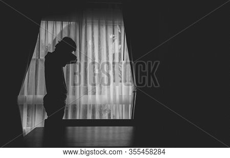 Alone Man Silhouette Standing At The Window Closed With Curtains In Darkroom. Man Stands At Window A