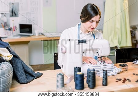 Portrait Of Pretty Young Woman Dressmaker With A Sewing Machine. Side View Photo Of Sewing Machine A