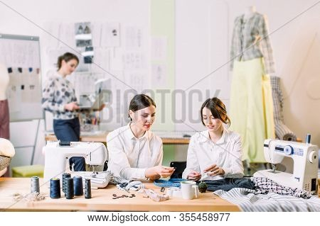 Fashion Design, Dressmaker, Tailor And Fashion Concept. Two Young Women Dressmakers Sewing While Sit